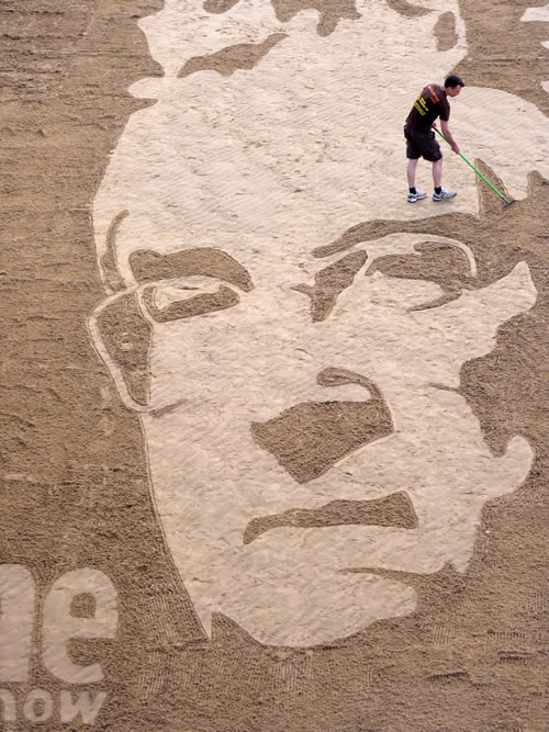 Tom Bolland puts the finishing touches to the Randy Newman Sand Drawing for the One Show