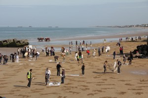 people on the beach doing sand drawings
