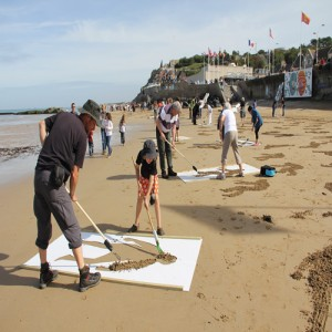 families drawing images on the beach