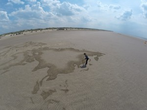 Claire Jamieson making a sand drawing on Southport beach