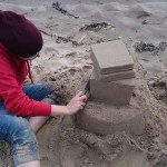 Jo carving some lovely detail into her stack of books sand sculpture