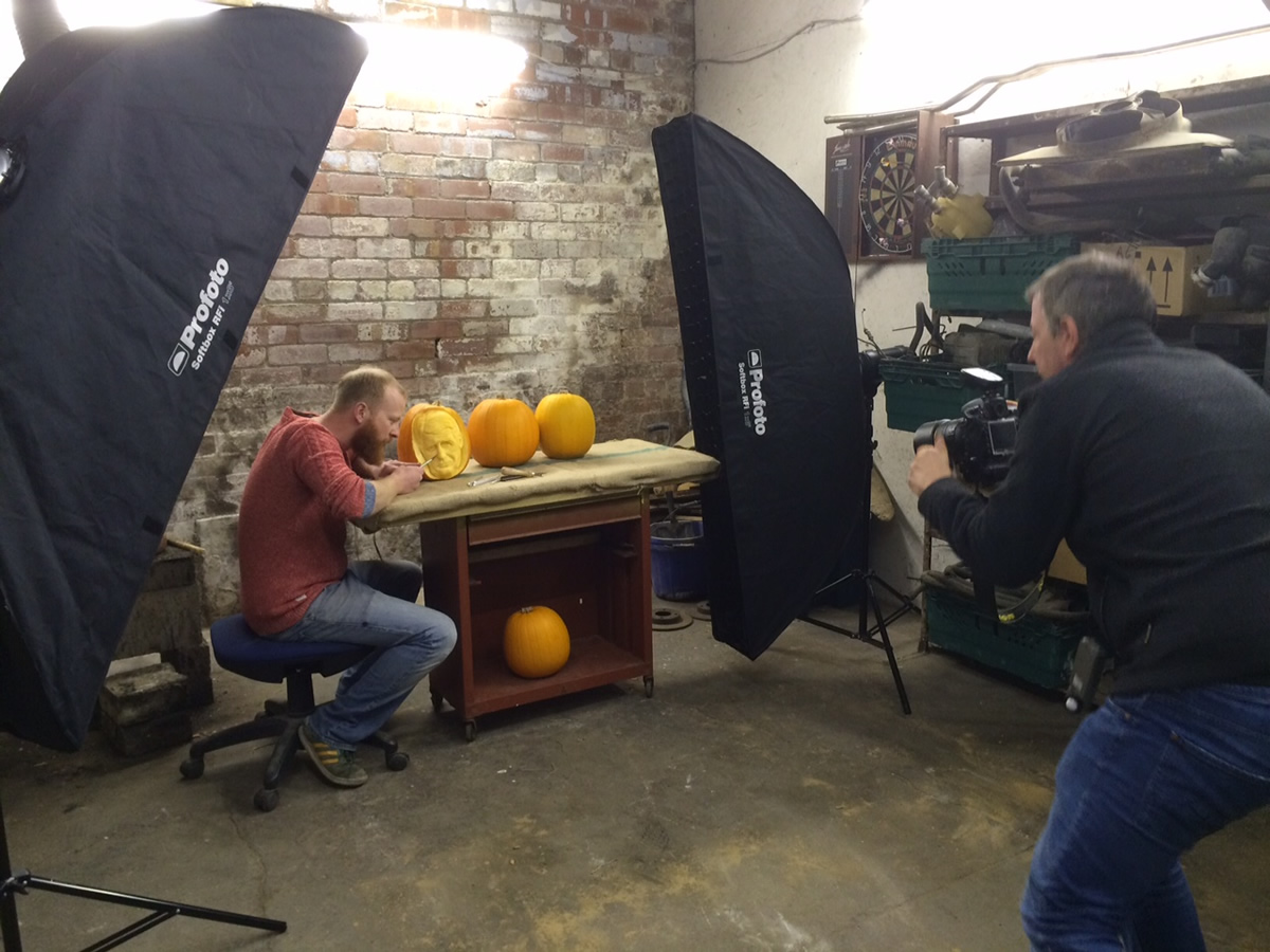 Professional pumpkin carver Jamie Wardley in the Sand In Your Eye workshop, posing with his pumpkins