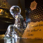 Dog looking on at the ice sculpture of a child in Manchester to raise awareness of homelessness