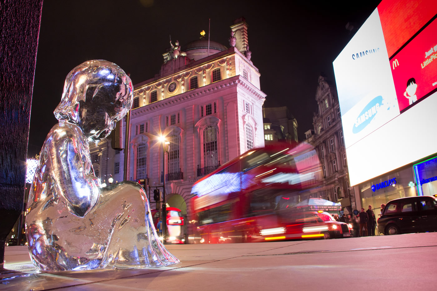 The final ice sculpture No.7 by the bright lights of Piccadilly Circus, with a bus rushing past. #pleaselookafterme