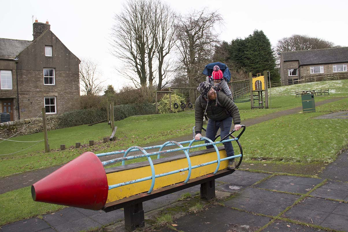 Jamie the big kid playing on the rocket in a playground in Hawes