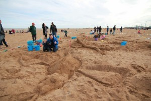 Sand sculpture competition winners with their dragon