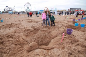 Sand sculpture competition winner with their turtle