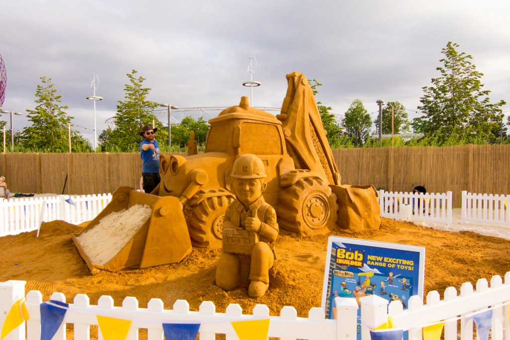 UK sand sculptor Jamie Wardley poses with the giant Bob The Builder sand sculpture at an urban beach event London