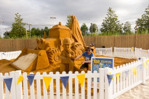 UK sand sculptor Jamie Wardley poses with the giant Bob The Builder sand sculpture at an urban beach at Olympic Park London