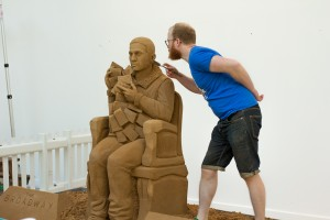 Jamie Wardley posing with Dynamo sand sculpture