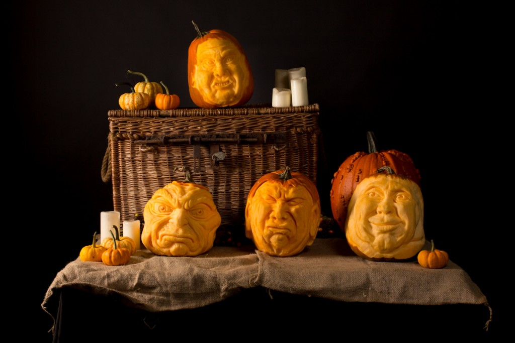 Professional pumpkin carvers create a series of pumpkin faces