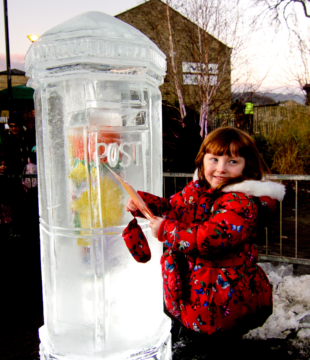 children posting their letters to Santa in the ice post box