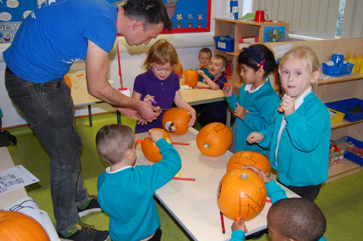 showing the children how to carve a pumpkin