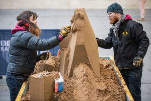 Sand sculptors Jamie and Claire working on the sand sculpture for BBC Radio 4