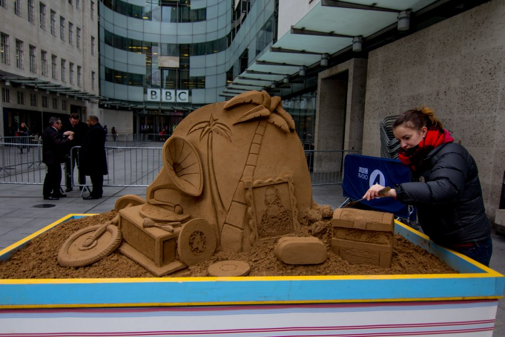 Sand sculptor Claire Jamieson with the sand sculpture created for BBC Radio 4