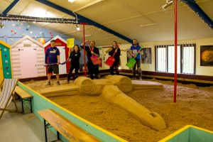 Team celebrate finished sand sculpture on their 1 day intensive sand sculpture course